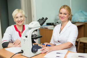 Елена Петрова и Марина Онышко (слева направо) проводят исследование крови под микроскопом.