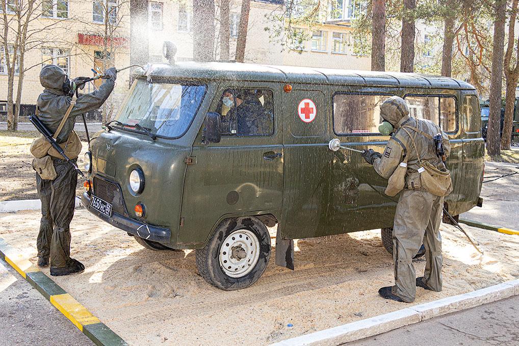 Обработка автомобиля скорой помощи дезинфицирующим раствором.